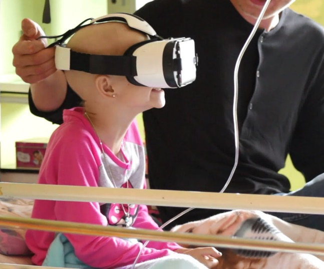 young girl patient with VR goggles in hospital bed